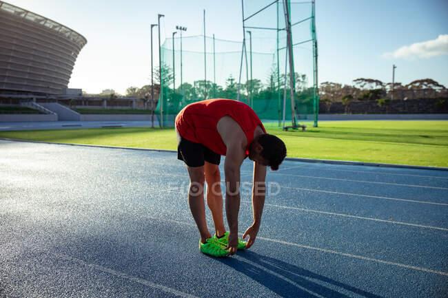 Вид сбоку на кавказского спортсмена в красном жилете, тренирующегося на спортивном стадионе, растягивающегося, наклоняющегося и трогающего пальцы ног на беговой дорожке — стоковое фото