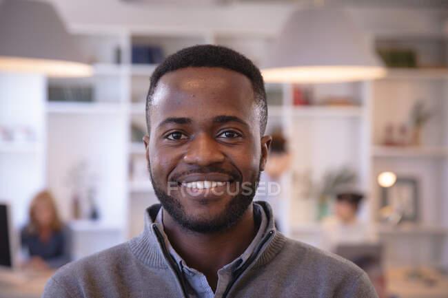 Ritratto di un felice uomo d'affari afroamericano che lavora in un ufficio moderno, guarda la macchina fotografica e sorride, con i suoi colleghi che lavorano sullo sfondo — Foto stock