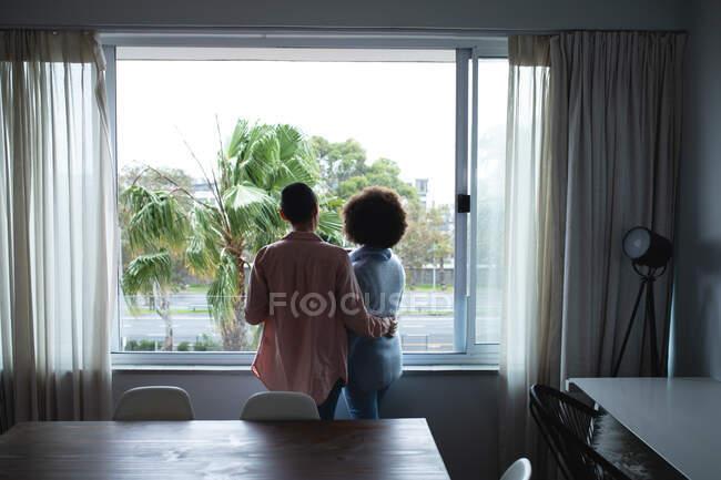 Передній вид змішаної раси Жіноча пара відпочиває вдома стоячи перед вікном у своїй їдальні і дивлячись на зовні, одна з її рукою навколо іншої. — стокове фото