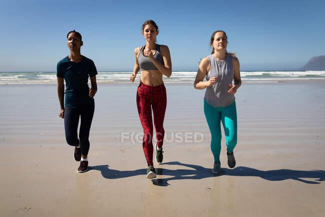 Вид спереди на многоэтническую группу подруг, наслаждающихся упражнениями на пляже в солнечный день, бегущих по берегу моря. — стоковое фото