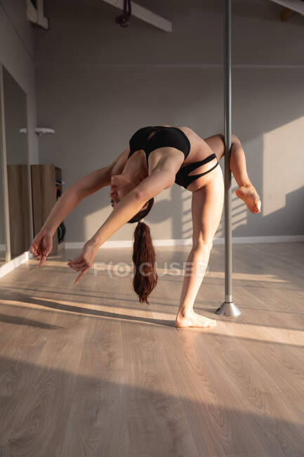 Вид спереди привлекательной белой женщины, наслаждающейся танцами на шесте в студии, держа шест ногой, растягиваясь и наклоняясь назад — стоковое фото