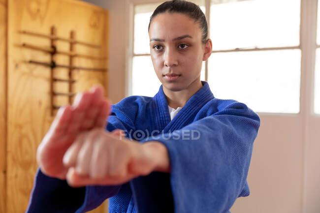 Передній вигляд зблизька фокусованої підліткової змішаної раси жіночої дзюдоки в блакитному дзюдо, розігрівається перед тренуванням в спортзалі, б'є позу, б'є повітря.. — стокове фото
