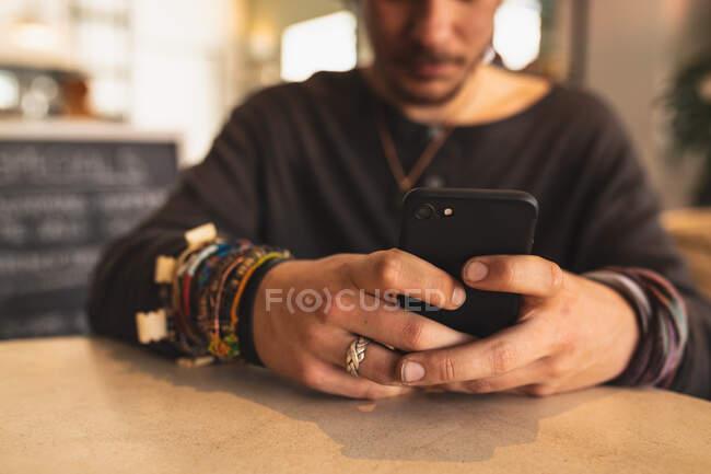 Vista frontale metà sezione di un uomo caucasico che indossa abiti casual, seduto accanto a un tavolo in una caffetteria e utilizzando il suo smartphone — Foto stock