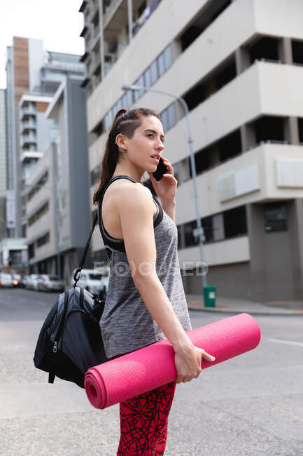 Side view of a fit Caucasian woman on her way to fitness training on a cloudy day, carrying a sports bag and a yoga mat, talking on a smartphone and waiting to cross the road — Stock Photo