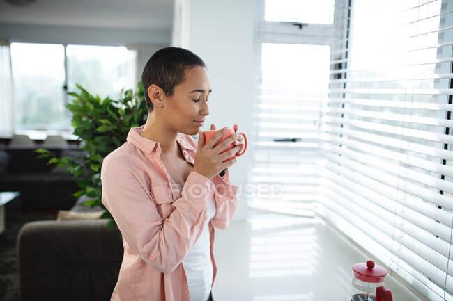 Vista laterale di una donna di razza mista con i capelli corti che si rilassa a casa, in piedi nel soggiorno vicino a un sedile finestra che guarda fuori dalla finestra, godendo di una tazza di caffè, con gli occhi chiusi e sorridenti — Foto stock