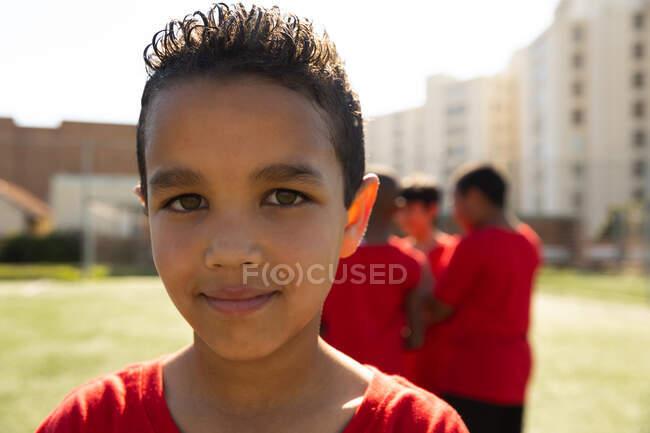 Портрет футболиста смешанной расы, одетого в свою команду, стоящего на игровом поле на солнце, смотрящего в камеру и улыбающегося, с товарищами по команде на заднем плане — стоковое фото
