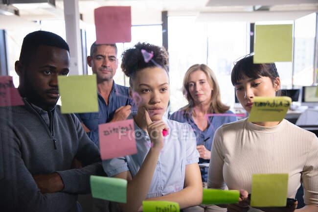 Різноманітна група ділових людей, які працюють у сучасному офісі, роблять мозковий штурм, пишучи на чистій дошці з примітками, які видно через — стокове фото