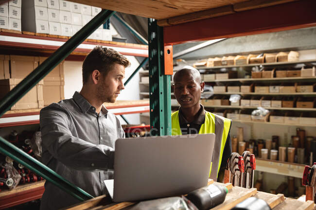 Caucasian male supervisor and African American factory worker wearing a high vis vest talking and using laptop. Workers in industry at a factory making hydraulic equipment. — Stock Photo