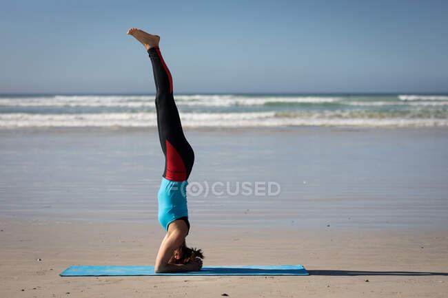 Вид сбоку на кавказскую привлекательную женщину, в спортивной одежде, практикующую йогу, стоящую в голове в положении йоги, на солнечном пляже. — стоковое фото