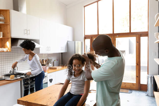 Front view of a young African American girl at home in the kitchen, sitting on the kitchen island while her father ties up her hair, the mother standing in the background cooking — Stock Photo