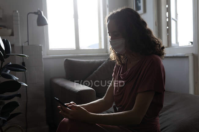 A Caucasian woman spending time at home, using her smartphone, wearing a face mask. Lifestyle at home isolating, social distancing in quarantine lockdown during coronavirus covid 19 pandemic. — Stock Photo