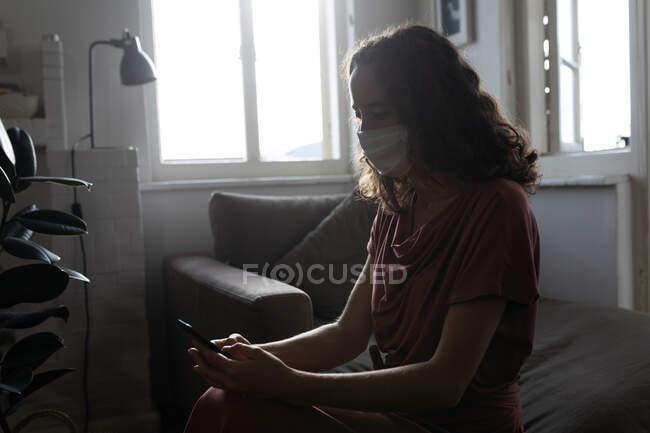 Une femme caucasienne passe du temps à la maison, utilisant son smartphone, portant un masque facial. Mode de vie à domicile isolement, éloignement social en quarantaine confinement pendant la coagulation du coronavirus 19 pandémie. — Photo de stock