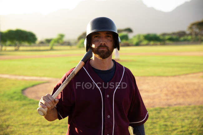 Портрет гравця в бейсбол у Кавказі, який одягнений в шолом на спортивному полі в сонячний день, тримаючи бейсбольну биту і відпочиваючи на плечі, дивлячись на камеру. — стокове фото