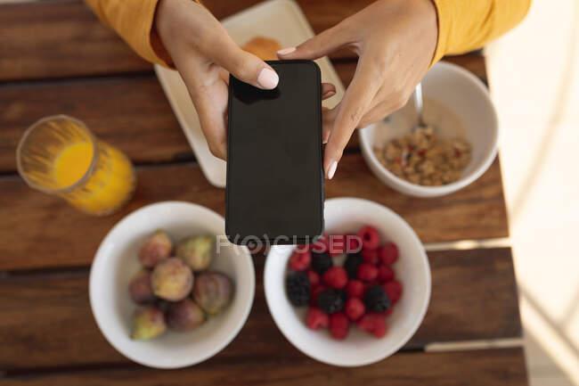 Femme assise près d'une table, prenant une photo du petit déjeuner avec son smartphone. Distance sociale et isolement personnel en quarantaine. — Photo de stock