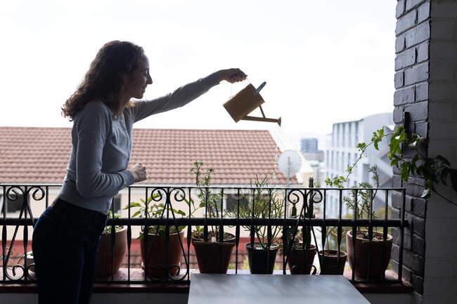 Una mujer caucásica pasando tiempo en casa, regando plantas en un balcón. Estilo de vida en el hogar aislamiento, distanciamiento social en cuarentena bloqueo durante coronavirus covid 19 pandemia. - foto de stock