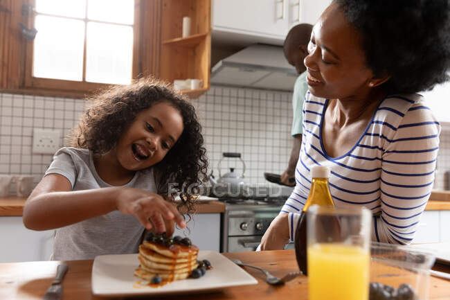 Front view close up of a young African American girl and her mother at home in the kitchen in the morning, sitting at the kitchen island, the girl playing with the pancakes on her plate and the mother laughing — Stock Photo