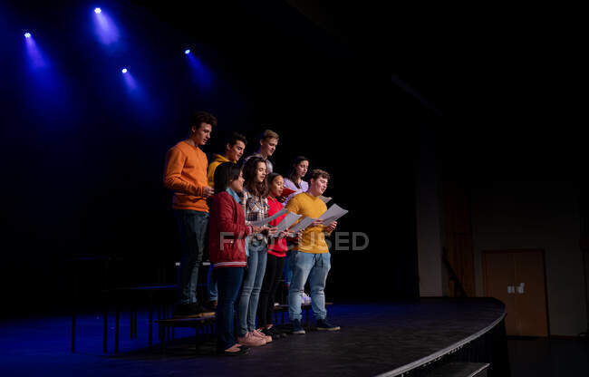Side view of a multi-ethnic group of teenage male and female choristers holding sheet music and singing standing on the stage of a school theatre during rehearsals for a performance — Stock Photo