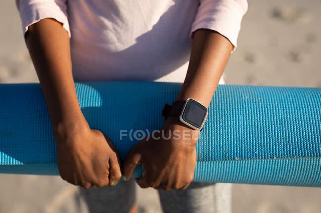 Передня частина жінки, стоячи на сонячному пляжі, одягнена в білу сорочку і тримаючи синій йога мат в руках, одягнена в чорний розумний годинник. — стокове фото