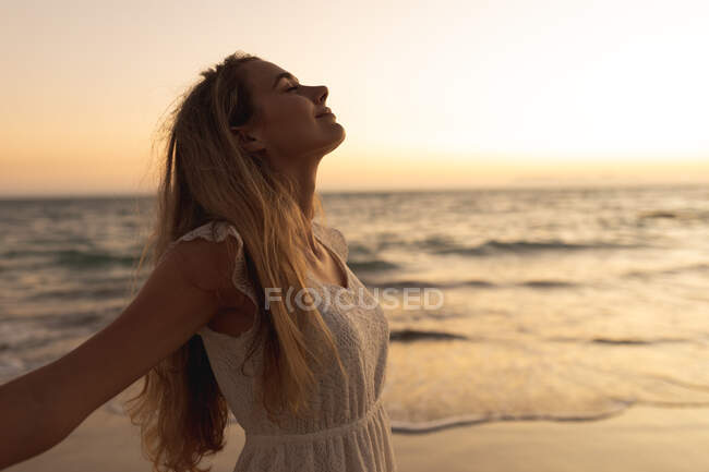 Caucasian woman standing barefoot on a beach during sunset, spreading her arms with eyes closed — Stock Photo