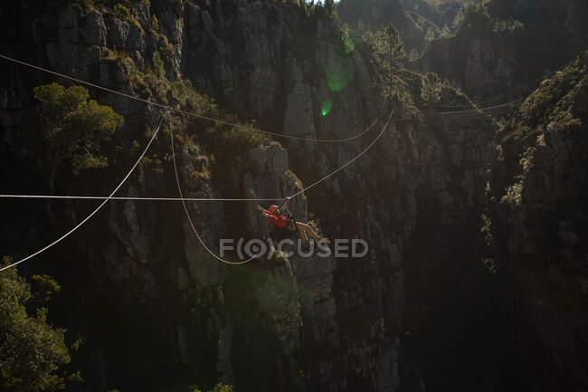 Vue latérale de l'homme caucasien profitant du temps dans la nature, tyrolienne par une journée ensoleillée dans les montagnes. Fun week-end aventure vacances. — Photo de stock