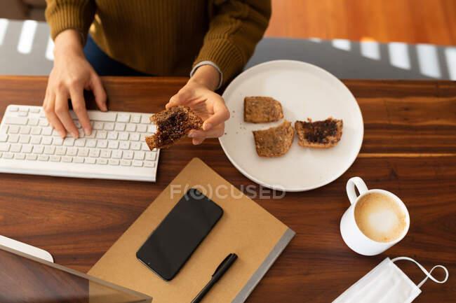 Manos de mujer pasando tiempo en casa, usando su computadora, comiendo. Estilo de vida en el hogar aislamiento, distanciamiento social en cuarentena bloqueo durante coronavirus covid 19 pandemia. - foto de stock