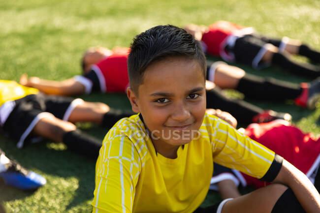 Портрет крупным планом молодого футболиста смешанной расы, сидящего на игровом поле в командном костюме, смотрящего в камеру и улыбающегося, с его товарищами по команде, отдыхающими после тренировки, лежащими на заднем плане — стоковое фото