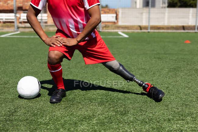 Низька секція чоловічого футболіста з протезом ноги в команді тренування на спортивному полі на сонці, підігріваючи розтягування ніг м'ячем поруч з ним.. — стокове фото