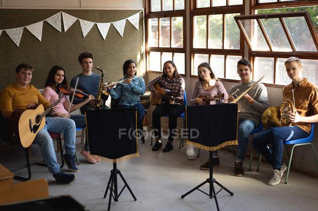 Portrait de groupe d'un groupe multi-ethnique de huit musiciens adolescents, hommes et femmes, assis dans une rangée dans une salle de classe tenant leurs instruments lors d'une pratique de la fanfare scolaire — Photo de stock