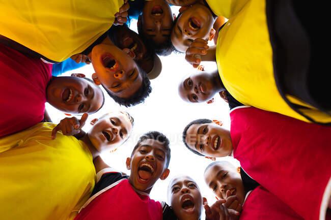 Plan rapproché à angle bas d'un groupe multiethnique de joueurs de soccer se tenant debout dans un câlin de motivation sur un terrain de jeu au soleil, les bras les uns autour des autres, s'embrassant et regardant vers le bas à la caméra souriant et riant avant un match — Photo de stock