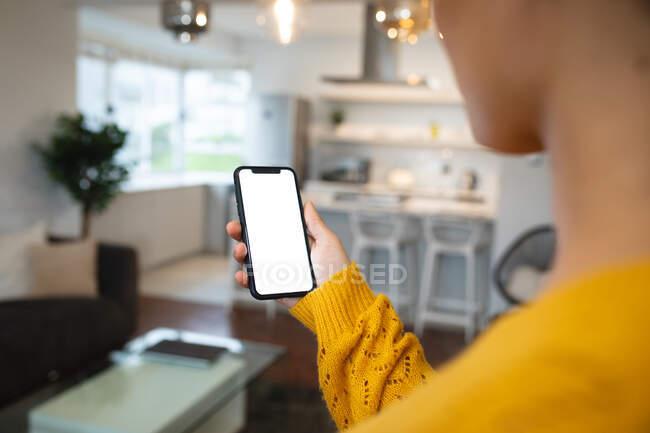 Через плечо вид смешанной расы женщина расслабляется дома, стоя в гостиной с помощью смартфона — стоковое фото