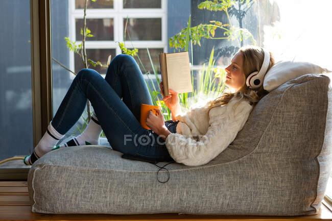 Vista lateral de una mujer caucásica sentada en su sala de estar frente a una ventana en un día soleado, leyendo un libro, usando auriculares y sosteniendo una taza - foto de stock