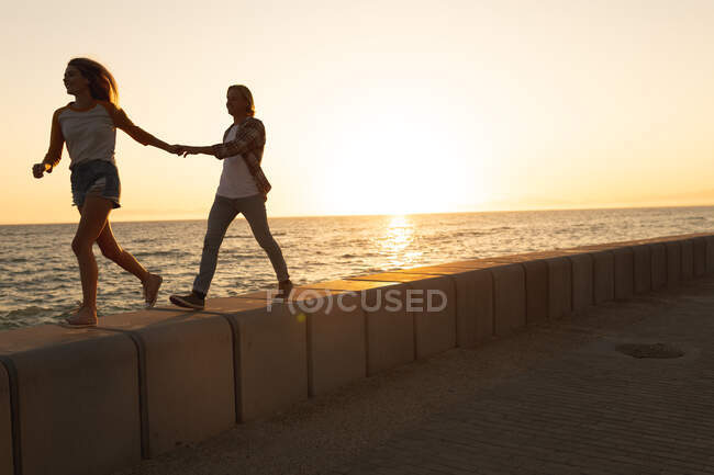 Caucasian couple walking on a promenade by the sea at sunset, holding hands, the woman leading. Romantic beach holiday couple — Stock Photo