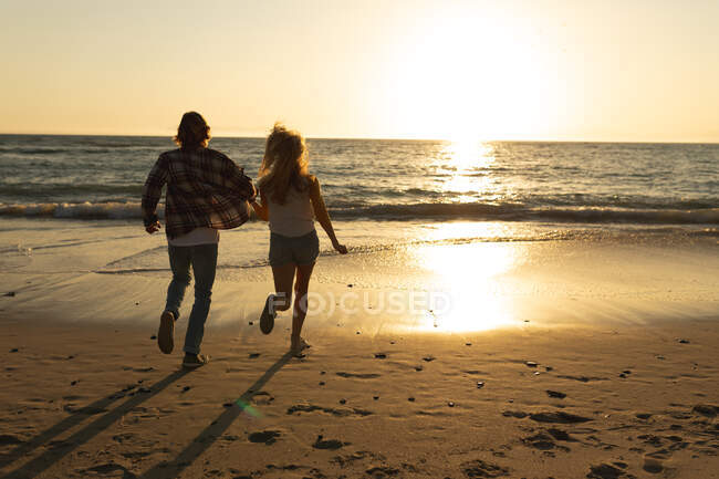 Caucasian couple running on a beach during a sunset, holding hands and looking at the sea — Stock Photo