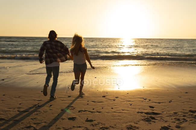 Coppia caucasica che corre su una spiaggia durante un tramonto, tenendosi per mano e guardando il mare — Foto stock