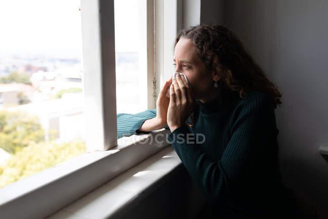 Una mujer caucásica pasando tiempo en casa, sonándose la nariz. Estilo de vida en el hogar aislamiento, distanciamiento social en cuarentena bloqueo durante coronavirus covid 19 pandemia. - foto de stock