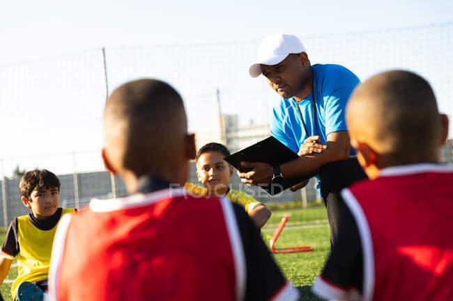 Sobre a visão do ombro de um treinador misto de futebol masculino se ajoelhando e instruindo um grupo multi-étnico de jogadores de futebol menino sentado em um campo de jogo ao sol durante uma sessão de treinamento de futebol — Fotografia de Stock