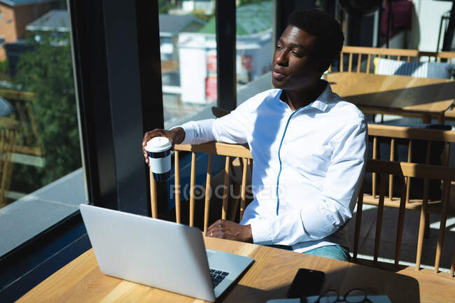 Афроамериканский бизнесмен, сидящий за столом в кафе, работающий над ноутбуком и думающий, держа чашку кофе — стоковое фото