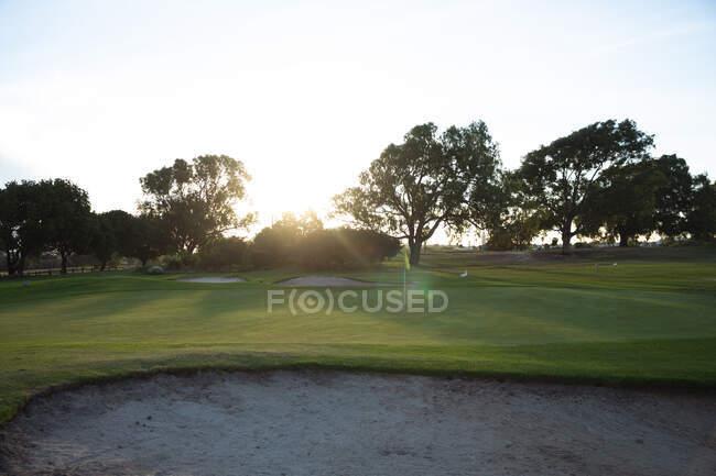 Sonnenuntergang über dem grünen Rasen eines Golfplatzes, versteckt hinter Bäumen, mit Bunkern auf dem Feld und gelber Flagge — Stockfoto