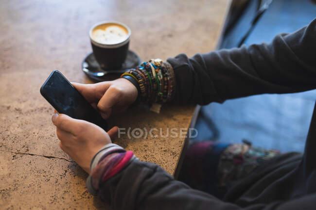 Вид сбоку средняя часть человека в повседневной одежде, сидя за столом в кафе, используя свой смартфон, с чашкой кофе стоя на столе. — стоковое фото