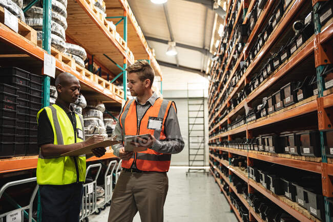 Caucasian and African American male factory workers wearing a high vis vest talking, holding tablet and clipboard. Workers in industry at a factory making hydraulic equipment. — Stock Photo