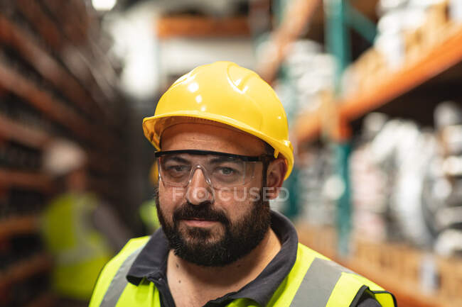 Portrait of a Caucasian male factory worker wearing a high vis vest looking at camera and wearing safety helmet. — Stock Photo