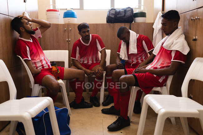 Multi ethnic group of male football players wearing a team strip sitting in changing room during a break in game, disappointed with towel around their shoulders. — Stock Photo