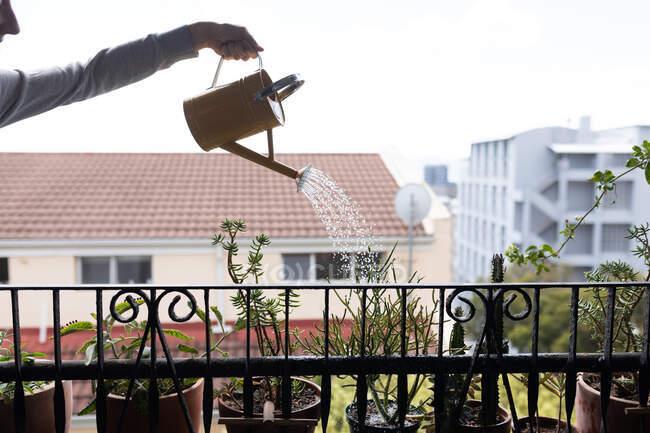 Mujer pasar tiempo en casa, regar las plantas en un balcón. Estilo de vida en el hogar aislamiento, distanciamiento social en cuarentena bloqueo durante coronavirus covid 19 pandemia. - foto de stock