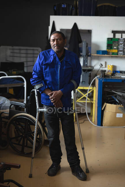 Portrait of a disabled African American male worker standing using crutches, wearing workwear, in a storage warehouse at a factory making wheelchairs, looking at camera — Stock Photo