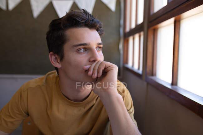 Портрет підлітка з Кавказу, який сидить за столом у шкільному класі і дивиться у вікно, думаючи — стокове фото