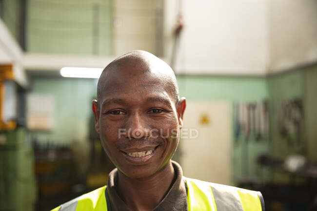 Portrait of an African American male factory worker wearing a high vis vest looking at camera and smiling. — Stock Photo
