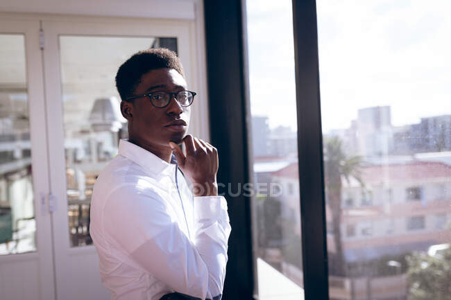 Portrait of an African American businessman, wearing a white shirt, working in a modern office, standing next to a window in the sun, touching his chin, looking at camera and thinking — Stock Photo