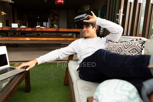 Front view of a Caucasian man hanging out on a balcony on a sunny day, wearing VR goggles, using a laptop — Stock Photo