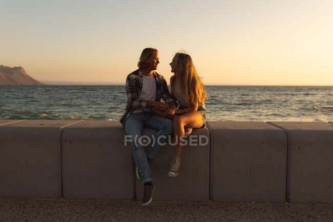 Coppia caucasica seduta su un muro su una passeggiata in riva al mare al tramonto, che si tiene per mano e si guarda. Romantica coppia di vacanze al mare — Foto stock