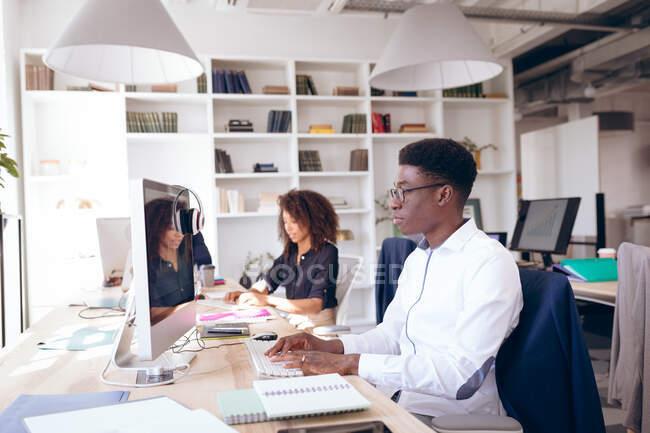 Un uomo d'affari afroamericano che lavora in un ufficio moderno, seduto a una scrivania e usando un computer, con una collega di lavoro donna che lavora sullo sfondo — Foto stock